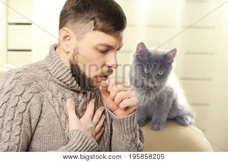 Ill man suffering from cough and pet on background. Concept of allergies to cats