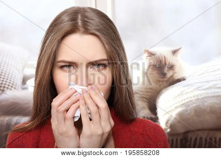 Young woman with tissue and pet on background. Concept of allergies to cats