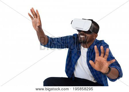 Man gesturing while using virtual reality headset against white background