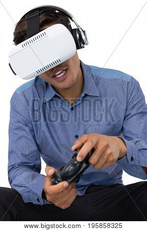 Young businessman using vr glasses while playing video game against white background