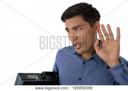 Young businessman cupping ears while standing against white background