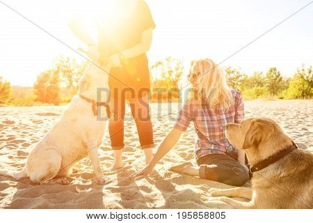 Two labrador friends playing on the beach. Two young women with two dogs in the sand. Sun flare