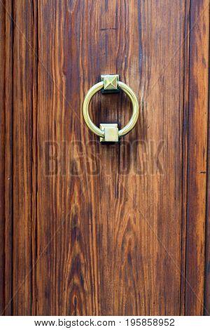 Antique brass door handle on a wooden door close-up
