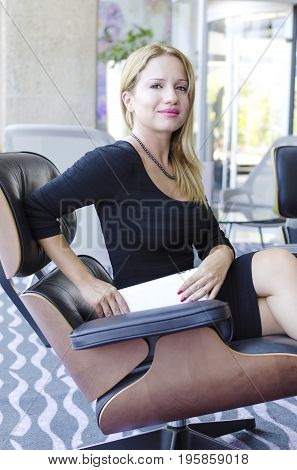 One modern beautiful young blonde white caucasian professional business woman smiling looking confident holding a tablet wearing a tight work office black dress sitting on a chair in a conference meeting room alone with big windows on background.