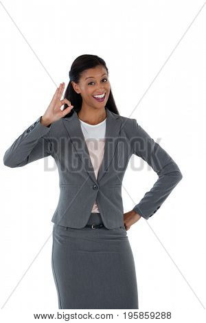 Smiling businesswoman gesturing okay hand sign