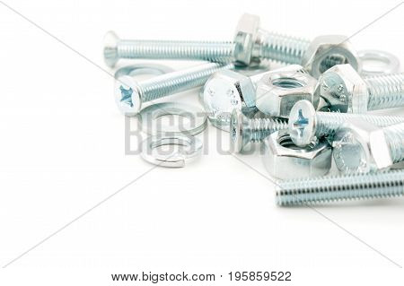 Scattered nuts and bolts on white background closeup