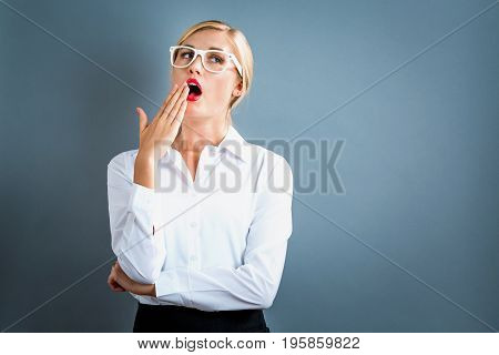 Young woman yawning on a gray background