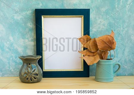 Blue and golden frame mockup concrete wall background wood table fry leaves aroma therapy lamp autumn fall tranquility relaxation