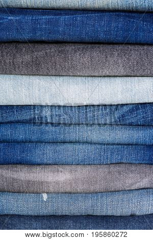 Closeup stack of folded clothes, blue jeans pants texture, dark blue denim trousers