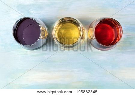 An overhead photo of three glasses of wine, red, white, and rose, on a teal blue background with a place for text