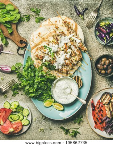 Summer barbecue party dinner set. Flatlay of grilled chicken skewers with yogurt dip, flatbreads, fresh parsley, vegetables, marinated olives and chilis over grey concrete table background, top view
