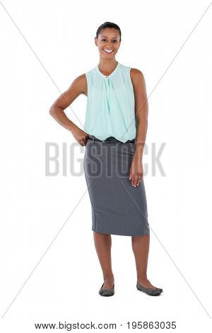 Smiling businesswoman standing with her hand on hips against white background