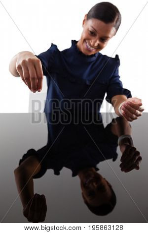 Smiling businesswoman pretending to work on an invisible object