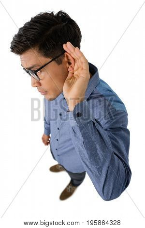 High angle view of businessman cupping ears while standing against white background
