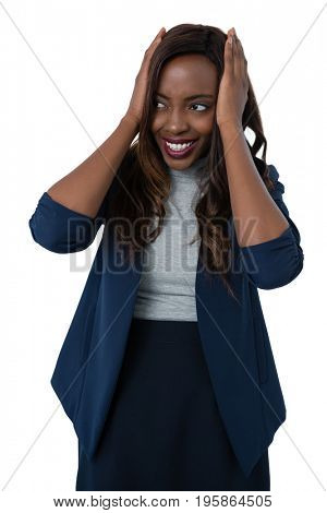 Smiling businesswoman with head in hand standing against white background