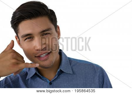 Portrait of young businessman gesturing call hand sign against white background