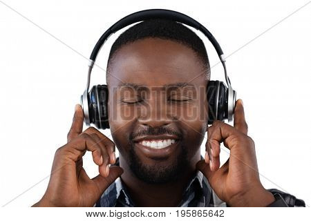 Happy man listening to music on headphones against white background