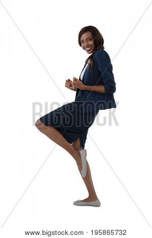 Side view of businesswoman standing on one leg against white background