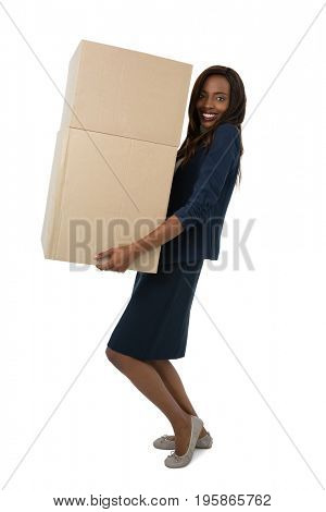 Portrait of businesswoman carrying cardboard boxes while standing against white background