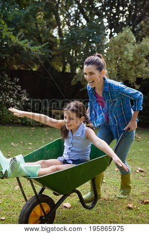 Happy woman pushing daughter with arms outstretched sitting in wheelbarrow in backyard