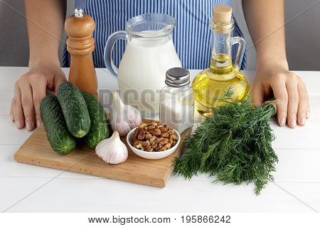 Fresh Ingredients For Cooking Tarator With Female Hands On White Wooden Table In The Kitchen.
