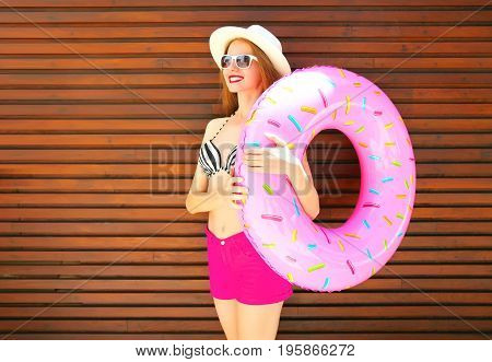 Summer Holidays Concept - Pretty Smiling Woman With Inflatable Ring On Wooden Background