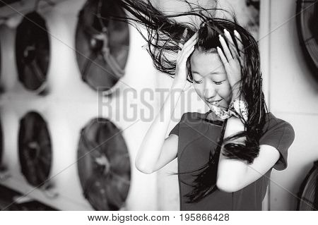 Young Beautiful Asian Woman, On The Background Of Industrial Air Conditioning System Fans. Portrait