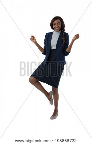 Portrait of happy businesswoman standing on one leg against white background