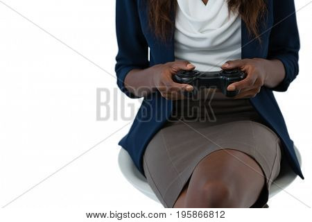 Mid section of businesswoman playing video game while sitting against white background
