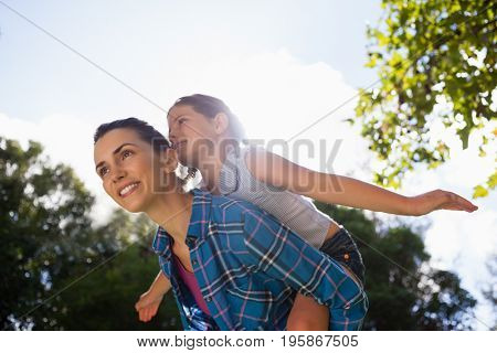 Low angle view of girl with arms outstretched enjoying piggyback ride on mother against sky in backyard