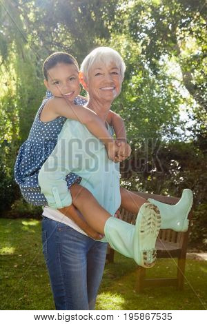 Portrait of grandmother giving piggyback ride to granddaughter against trees in backyard
