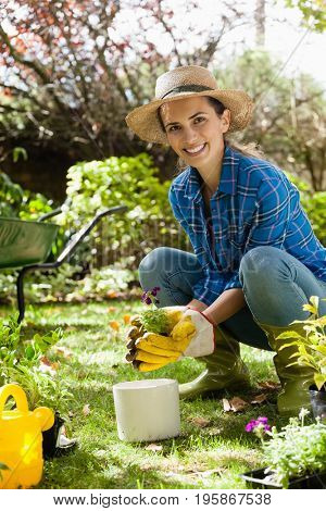Portrait of smiling woman planting seedling while crouching on field at backyard