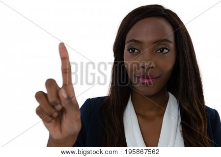 Confident businesswoman touching imaginary screen against white background