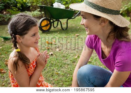 Smiling mother and daughter talking on field in backyard