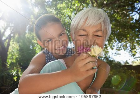 Grandmother smelling flowers held by granddaughter while piggybacking her in backyard