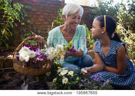 Smiling grandmother holding flower basket while talking to granddaughter in backyard