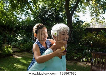 Smiling senior woman carrying granddaughter holding flowers in backyard