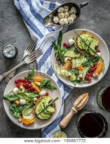 Vegetarian dinner - salad and wine on a dark background