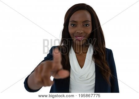Smiling young businesswoman touching imaginary screen against white background