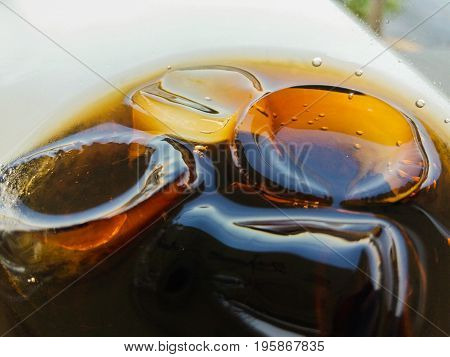 cola in the glass with ice close up refreshing soft drink