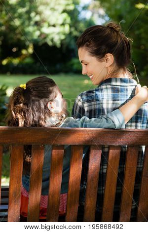 Smiling woman looking at daughter with arm around on wooden bench at backyard