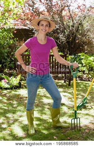 Portrait of smiling beautiful woman holding gardening fork at backyard