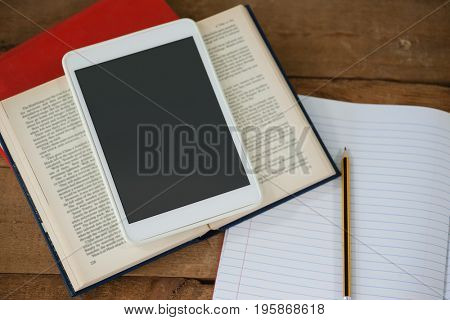 Close-up of digital tablet and books on table in classroom at school