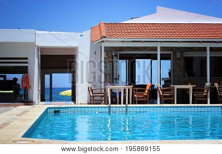 Swimming pool filled with water close up in the apartment. In the background a bar and a path to the sea.