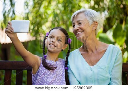 Smiling girl and grandmother taking selfie in backyard