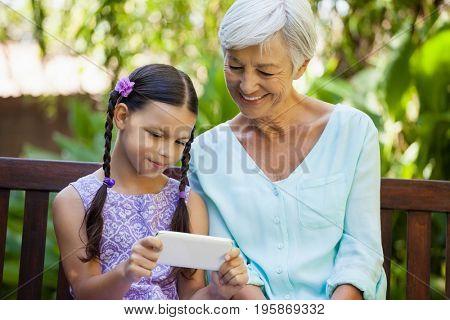 Smiling senior woman looking at girl using mobile phone at backyard