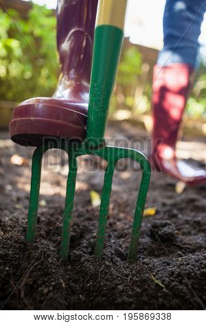 Low section of senior woman standing with garden fork on dirt at backyard
