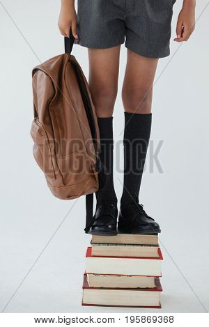 Low section of schoolboy standing on stack of book against white background