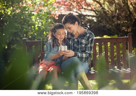 Girl showing mobile phone to mother while sitting on wooden bench at backyard