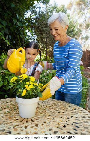 Smiling senior woman standing by granddaughter watering yellow flowers on table at backyard